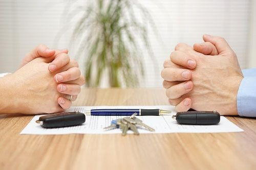 Close up of a pair of hands across from each other, resting on a piece of paper on a table with a pen, two key fobs and set of keys.